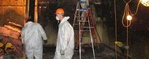 Fire Damage Restoration Technician Working In Garage