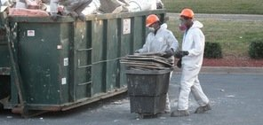 Water and Mold Damage Restoration Technicians Removing Debris To Street Dumpster